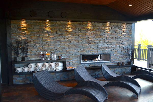 Relaxstolar mot en belyst stenvägg.