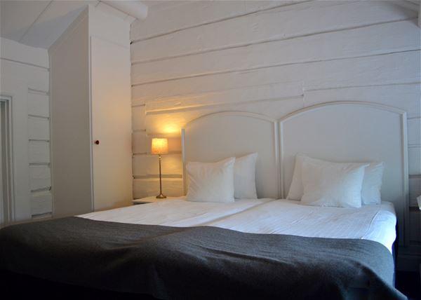 Dubbelsäng med vit sängram mot en vitmålad brädvägg.
