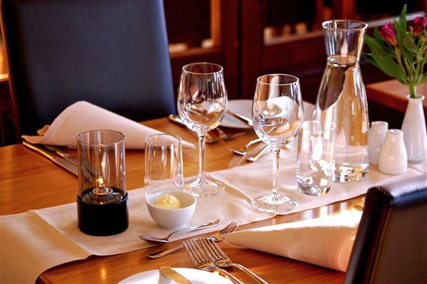 Dukat bord i restaurangen med vita servetter, vinglas och en karaff vatten.