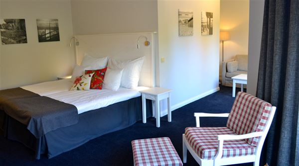 Ett rum med en säng med vit sänggavel och en rödrutig fåtölj.
