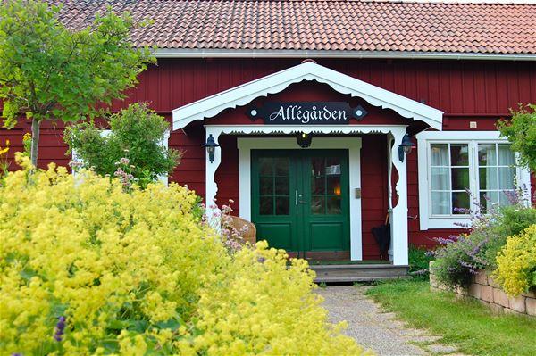 Exteriör av allégårdens entré med en grön dubbeldörr, på det röda huset med vita knutar och fönster.