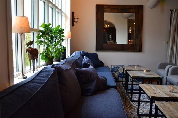 Blå stor loungesoffa vid fönstret och flera soffbord av ek framför.