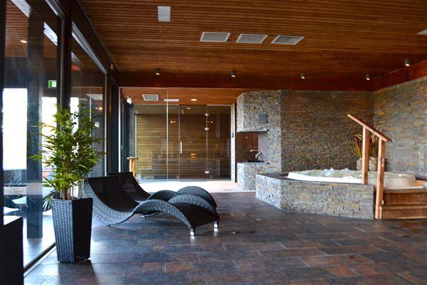 Två relaxstolar som står vid stora fönster och en bubbelpool.