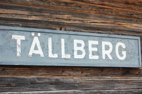 Skylt med namnet Tällberg sitter på en brun timmervägg.