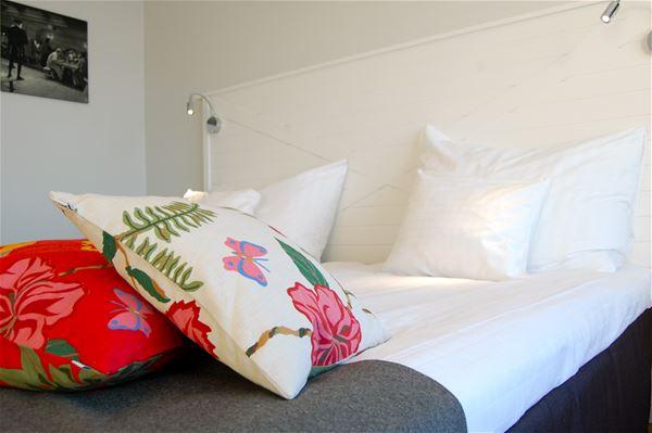 Säng med vita och röda, blommiga kuddar ovanpå.