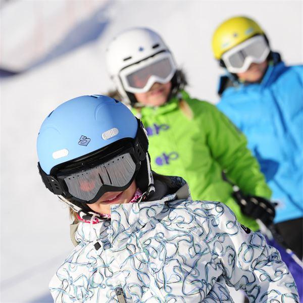 Tre barn i slalomhjälmar.