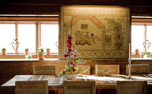 Långbord med dala stolar i salong med traditionell kurbits målning på väggen.