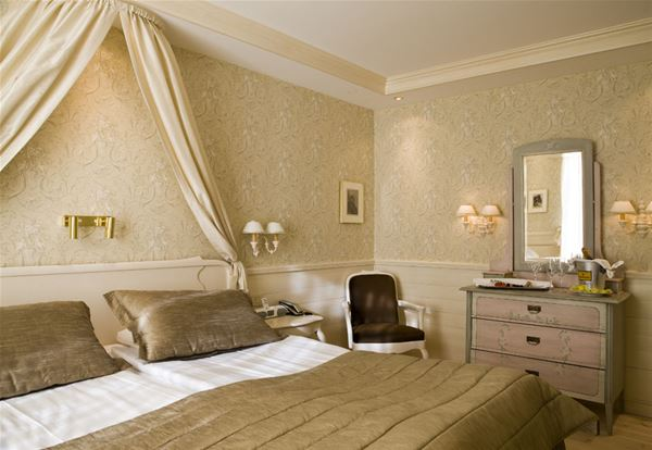 Hotellrum med dubbelsäng, byrå, spegel och en rokokofåtölj.