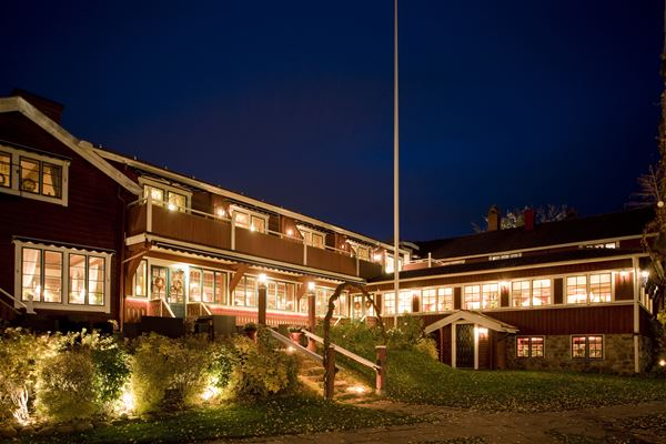 Hotellet från innergården med massor med fönster som lyser upp i kvällsmörkret.