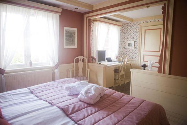 Hotellrum med dubbelsäng, skrivbord, två fönster.