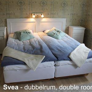 Rum med dubbelsäng och två sängbord.