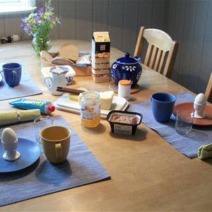 Uppdukad frukost vid köksbordet.