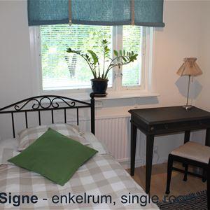 Enkelrum, säng, sängbord och stol.
