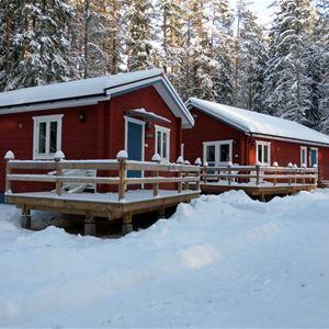 Två stugor med verandor en vinterdag.