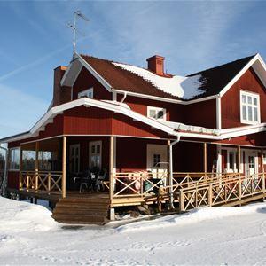 Röd villa med stor altan en vinterdag.