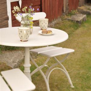 Cafébord med två stolar och fika uppdukat.