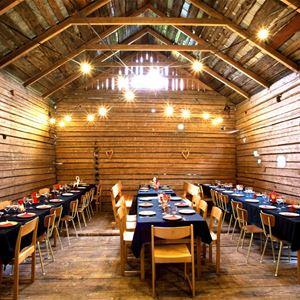 Festlokal i ladan med uppdukade långbord.