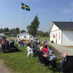 Människor som sitter på en gräsplätt under en Sverigeflagga