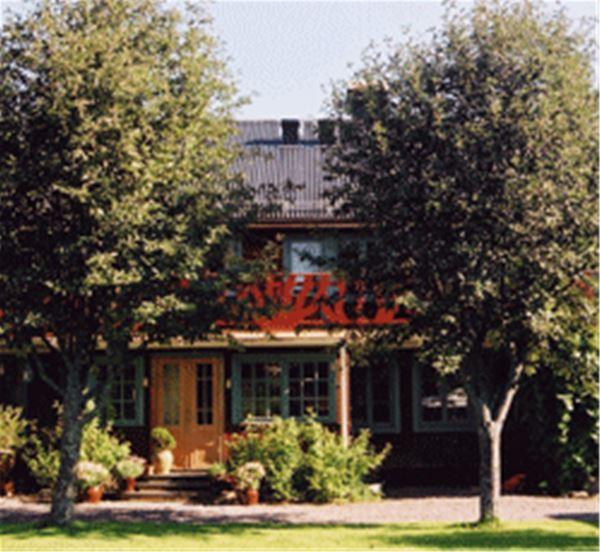 Del av byggnaden bakom träden.