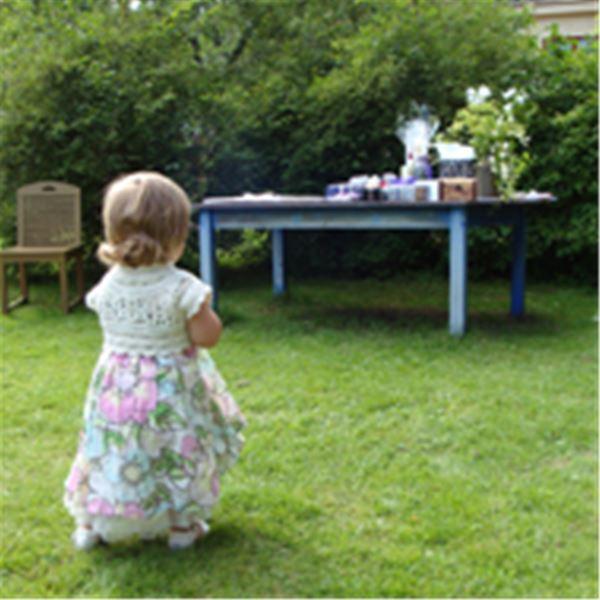 Liten flicka i klänning på gräsmattan.
