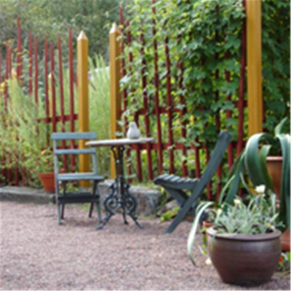 Cafébord och stolar i trädgården.