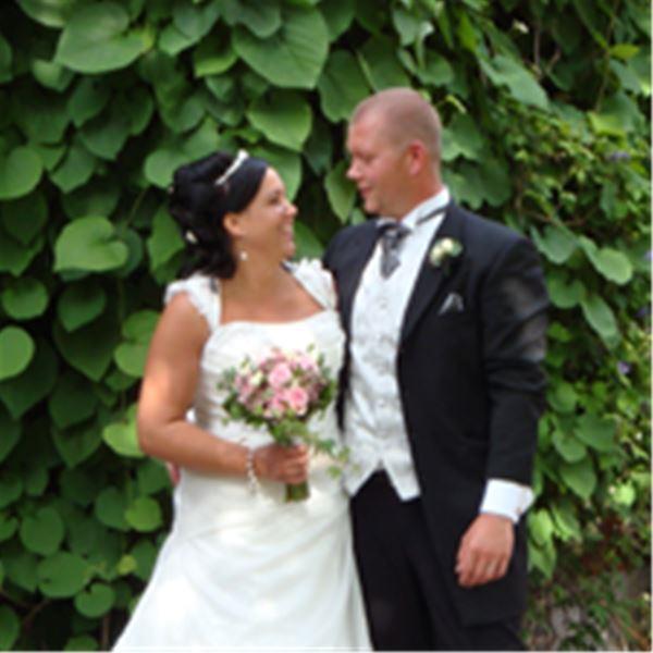 Bröllopspar fram för en grön häck.