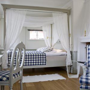 Rum med en dubbelsäng som har en sänghimmel.