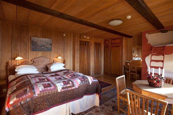 Dubbelsäng med lapptäcke som överkast i ett rum med golv, väggar och tak av furu.