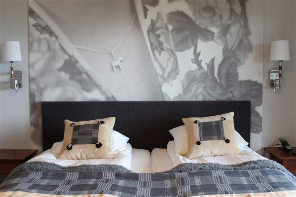 Dubbelsäng med svart sänggavel och grå-rutigt överkast.