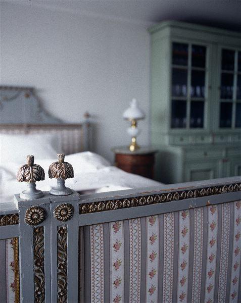 Detalj från en grå sängram med bård och knoppar av metall samt stoppad gavel.
