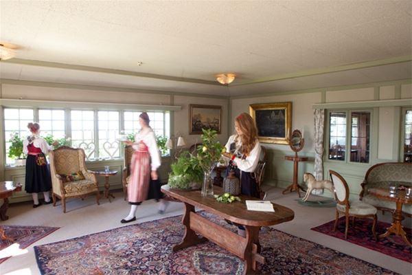 Tre kvinnor i folkdräkt rör sig i en Salong med stora fönster, stor matta på golvet och antika möbler.