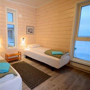 Bildet er tatt på innsiden av leiligheten. Den viser soverommet, der det er redd opp to senger, en på hver side av rommet.