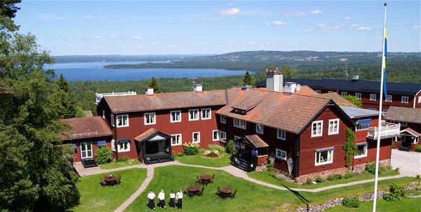 Villa Långbers från ovan en solig sommardag med sjön  Siljan i bakgrunden och en flaggstång framför den faluröda träbyggnaden.
