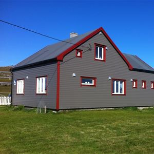 Bildet er tatt at Emelie huset på Ekkerøy, Ekkerøy feriehus. Grønn plen, å nydelig blå himmel i bakgrunnen. Huset er ganske så stort å et grå og rød malt.