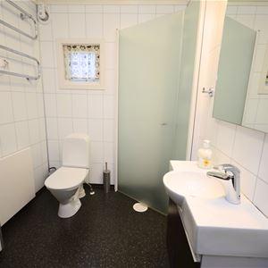På bildet ser du badet. Det er dusj hjørne, servant og speil, å et toalett.