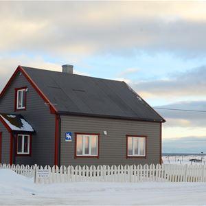 Bildet er tatt at Emelie huset på Ekkerøy, Ekkerøy feriehus. Det er snø på utsiden av det grå og rød malte huset.