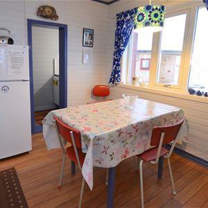 Bildet er tatt på innsiden av Emelie huset. Inne på kjøkkenet, med et lite spisebord å et stort kjøleskap, med liten frys.