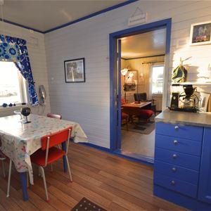 Bildet er tatt på innsiden av Emelie huset. Inne på kjøkkenet, med et lite spisebord, å man ser også de fine blåmalte kjøkkenskapene.