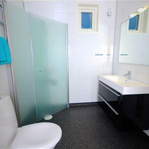 Bildet er tatt på innsiden av leiligheten å viser badet. Det er dusj, vask, speil og toalett