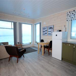 Bildet er tatt på innsiden av leiligheten. Du ser stuen, med sofa og spise møbler. Store vinduer.