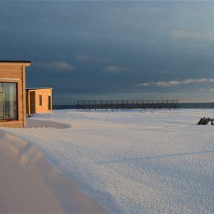 Bildet er tatt på utsiden av leilighetene. To leiligheter vises på bildet. Bildet er tatt på vinteren så det er snø dekke på utsiden. Det står fiskegjeller i bakgrunnen.