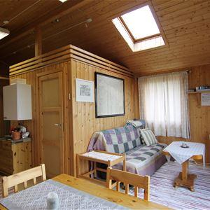 Bildet er tatt på innsiden av hytten å viser en liten sofa krok. En sofa og et bord samt et sidebord.