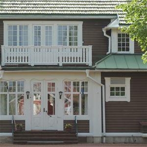 Entrén på Trunna Vandrarhem och konferens med vit dubbeldörr, spröjsade fönster och balkong med vitt räcke.