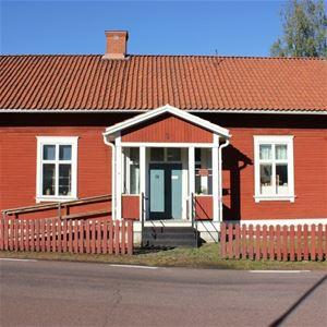 Rödmålat hus med vita foder och blå dörr.