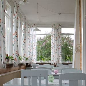 Verandafönstren med vita blommiga gardiner, blommor i fönstren och bord med stolar.