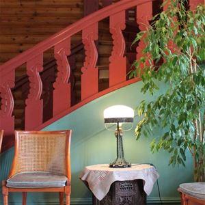 Detalj på rödmålat trappräcke med en stol och ett litet bord med lampa framför.