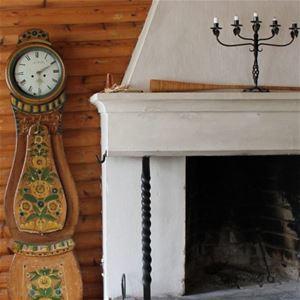 Detalj på öppenspis med ljusstake på spishällen och en gammal dalmålad klocka bredvid.
