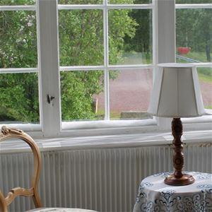 Detalj på spröjsade fönster, litet bord med lampa.