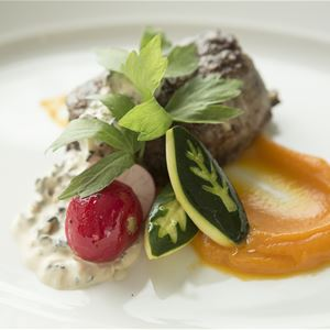Köttbit med grönsaker och såser vackert upplagt.