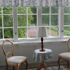 Spröjsade fönster med två stolar i trä och ett litet bord med duk och lampa framför fönstret.